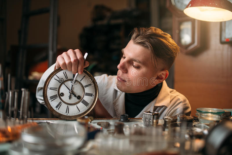 De horlogemaker past het mechanisme van oude horloges aan stock foto