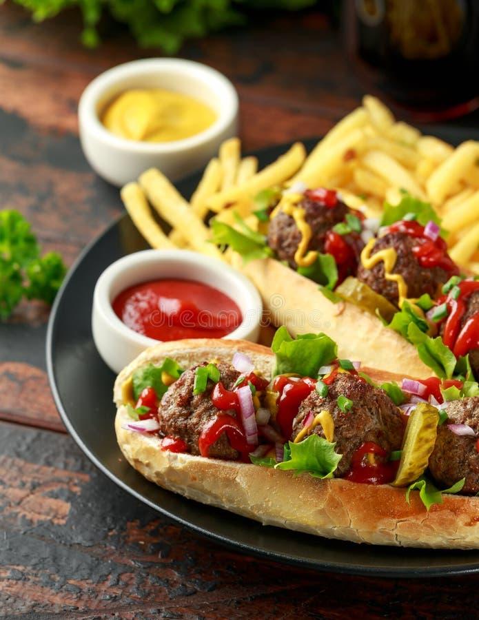 De hotdogs van vleesballen met Franse aardappelgebraden gerechten, spaanders, kreuk snijden augurken, ketchup en mosterd Snel voe stock afbeeldingen