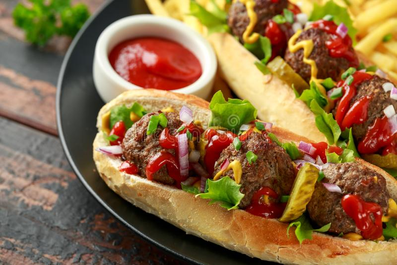De hotdogs van vleesballen met Franse aardappelgebraden gerechten, spaanders, kreuk snijden augurken, ketchup en mosterd Snel voe stock foto's