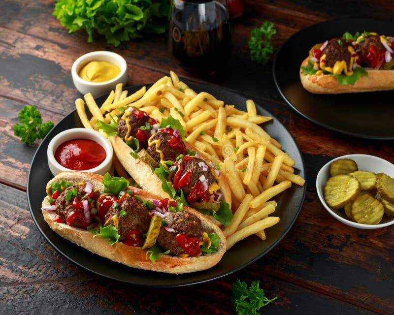 De hotdogs van vleesballen met Franse aardappelgebraden gerechten, spaanders, kreuk snijden augurken, ketchup en mosterd Snel voe royalty-vrije stock fotografie