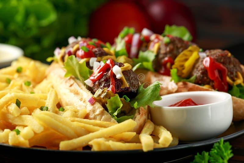 De hotdogs van vleesballen met Franse aardappelgebraden gerechten, spaanders, kreuk snijden augurken, ketchup en mosterd Snel voe stock afbeelding