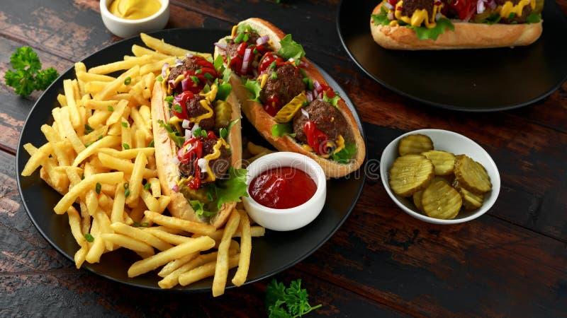 De hotdogs van vleesballen met Franse aardappelgebraden gerechten, spaanders, kreuk snijden augurken, ketchup en mosterd Snel voe royalty-vrije stock afbeeldingen