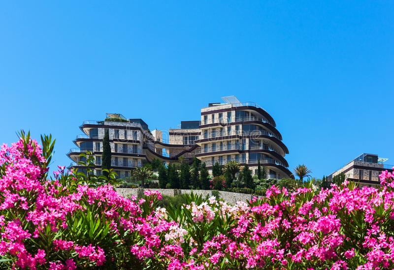 De hotelbouw onder bloemen en groen tegen blauwe hemel stock afbeelding