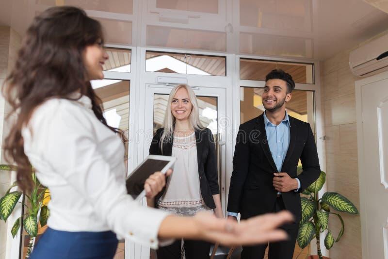 De hotelreceptionnist Meeting Business Couple in Hal, de Man van de Zakenluigroep en de Vrouwengasten komen aan stock afbeeldingen