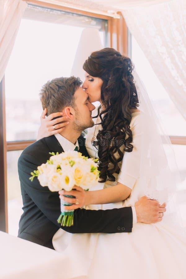 De houdende van bruid kust haar nieuw echtgenootvoorhoofd, zittend op zijn knieën Venster bij achtergrond royalty-vrije stock fotografie