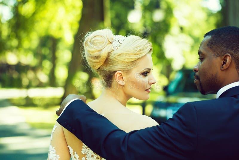 De houdende van bruidegom raakt schouder van aanbiddelijke bruid royalty-vrije stock afbeeldingen