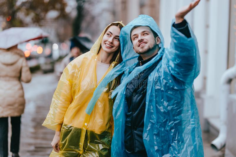 De houdende van kerel en het meisje in de gele en blauwe regenjassen lopen op de straat in de regen royalty-vrije stock fotografie