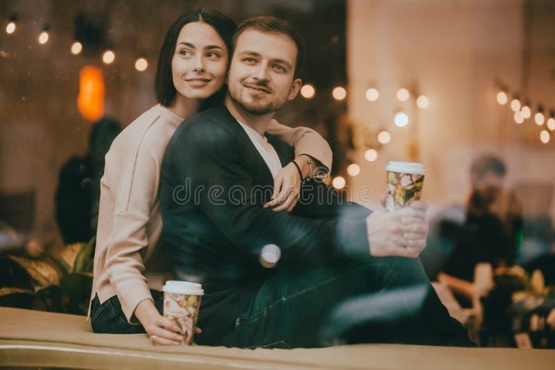 De houdende van kerel en het meisje zitten het koesteren op de vensterbank in een romantische koffie royalty-vrije stock afbeelding