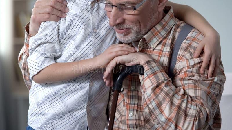 De houdende van kleinzoon die grootvader omhelzen, geeft en steun voor oudere generatie royalty-vrije stock foto
