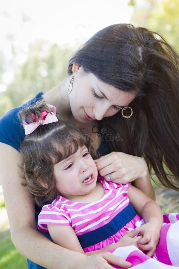 De houdende van Moeder troost Schreeuwende Babydochter stock foto's