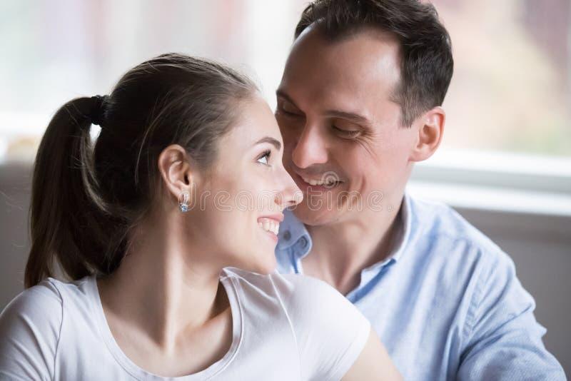 De houdende van vrouw die van de echtgenootomhelzing van rug elkaar bekijken stock afbeeldingen