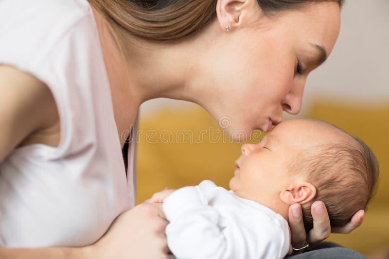 De houdende van Zoon van de Moeder Knuffelende Baby en het Geven van hem Kus op Voorhoofd royalty-vrije stock afbeeldingen