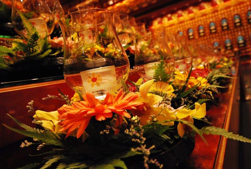 De houders van de glaskaars bij een altaar baadden in amber binnenlandse lichten stock foto