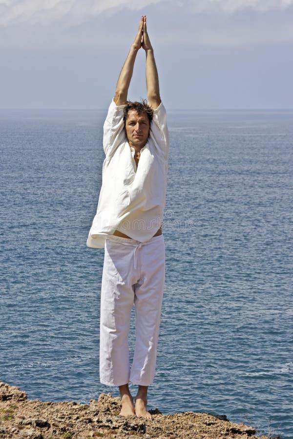 De houding van de yoga op de rotsen stock foto
