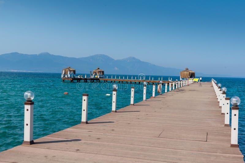 De houten as is in een zonnig strand Blauwe hemel en berg op de achtergrond Vakantie en vakantie op strandconcept stock foto