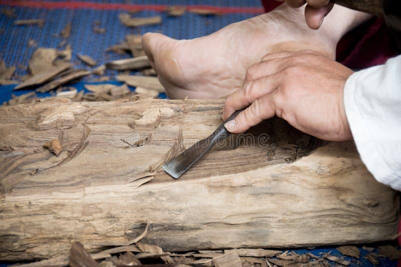 De houten beeldhouwermens gebruikt een houten beitel aan uittreksel royalty-vrije stock foto's