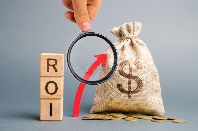 De houten blokken met het woord ROI en de omhooggaande pijl met het geld doen in zakken Hoog niveau van bedrijfsrentabiliteit Ren royalty-vrije stock afbeeldingen