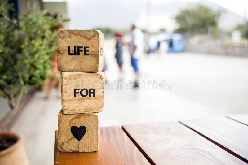 De houten blokken met de woorden liggen op de lijst Houten kubussen met brieven en symbolen Het leven voor liefde royalty-vrije stock fotografie