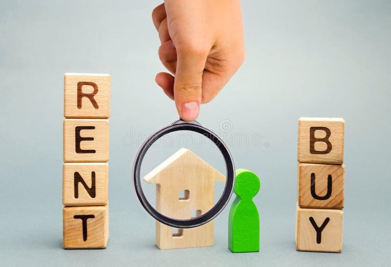 De houten blokken met de woordhuur of kopen en een persoon bevindt zich dichtbij het huis Neem het juiste besluit Concept 6 van o stock foto