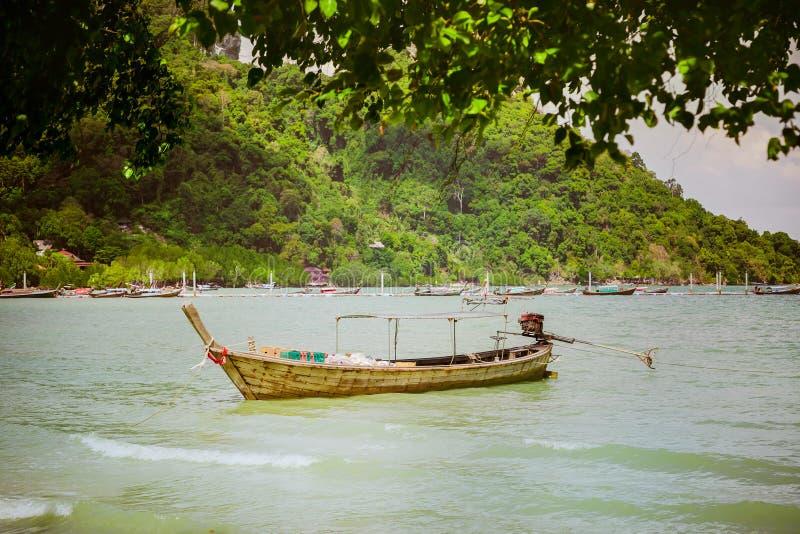 De houten boot levert producten en goederen aan de kust Huisvuilverwijdering Het eiland, het probleem van voedsellevering stock afbeeldingen