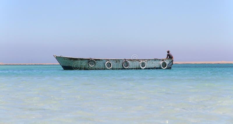 De houten boot op Paradise-eiland in Rood ziet, Egypte met boatman royalty-vrije stock fotografie