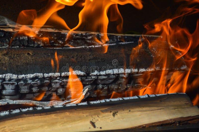 De houten brandende hete verkoolde planken van hout opent een brand met tongen van brand en rook het programma Textuur, achtergro stock fotografie