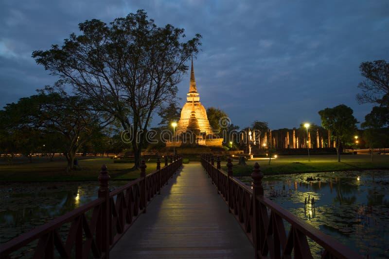 De houten brug die aan ruïnes van de oude Boeddhistische tempel van Wat Sa Si in avondschemering leiden Sukhothai, Thailand stock afbeeldingen