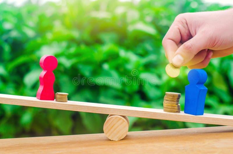 De houten cijfers van een man en een vrouw bevinden zich op de schalen en de muntstukken tussen hen het concept het geslacht beta royalty-vrije stock foto's