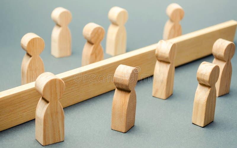 De houten cijfers van mensen worden gescheiden door een barrière sociale klassen Concurrentie tussen teams het concept misverstan stock foto's