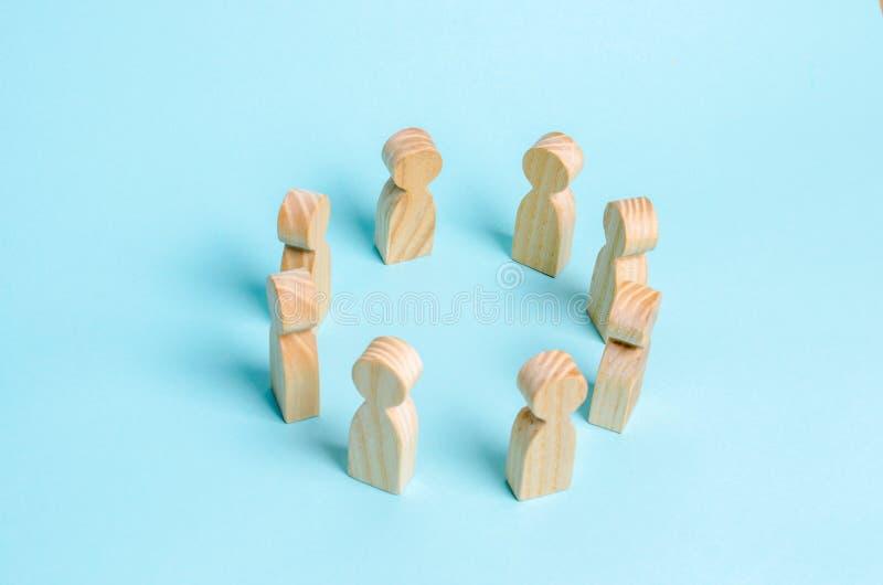 De houten cijfers van mensentribune in een cirkel en leiden een gesprek Het concept mededeling en samenwerking van arbeiders royalty-vrije stock foto's