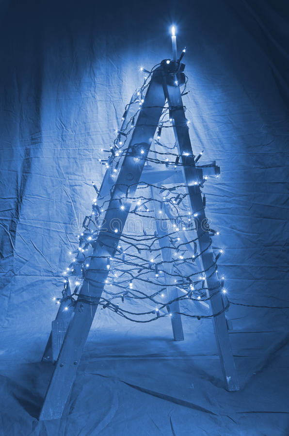 De houten die ladder met Kerstmislichten wordt verfraaid De vorm van stock fotografie
