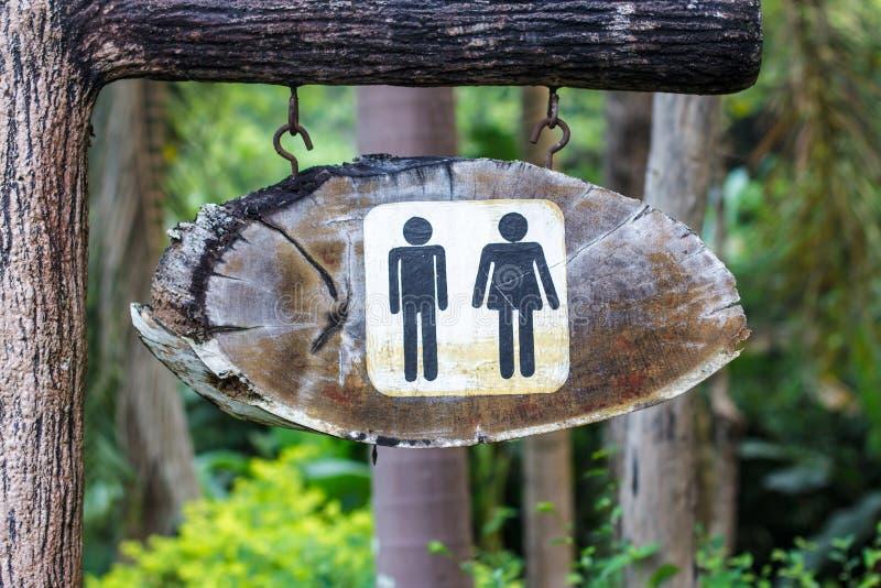 De houten ingang van de teken hangende badkamers stock afbeeldingen