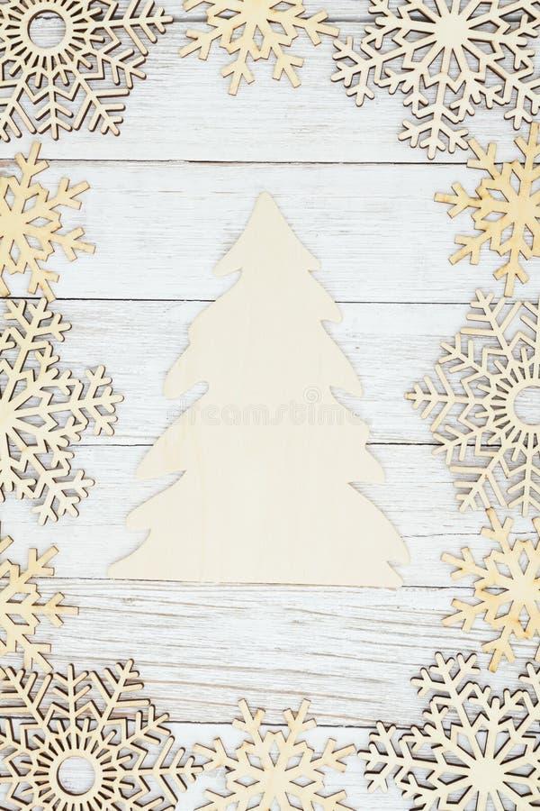 De houten Kerstboom met houten sneeuwvlokken op doorstaan vergoelijkt geweven houten achtergrond stock foto's