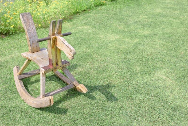 De houten kinderen van de hobbelpaardstoel op gazon stock fotografie