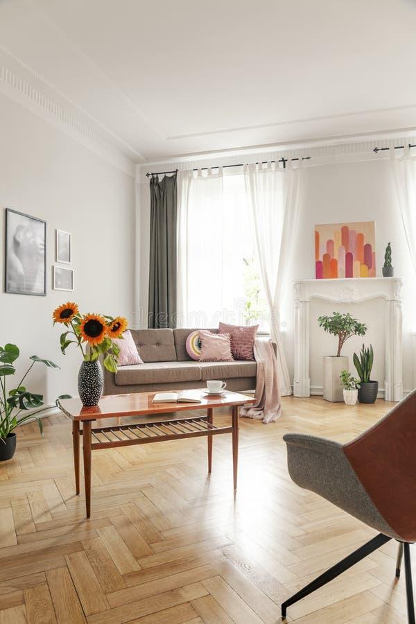 De houten koffietafel met verse zonnebloemen, het open boek en de thee vormen in echte foto van helder woonkamerbinnenland tot ee stock afbeelding