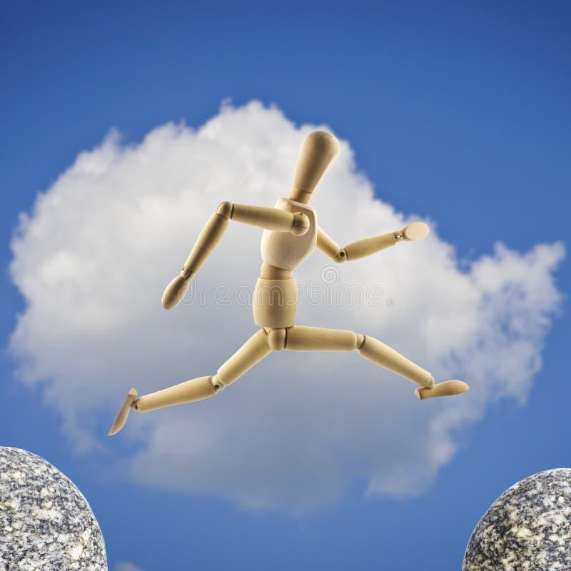 De houten ledenpop springt over het kloof bij bewolkte hemelbackgro stock fotografie