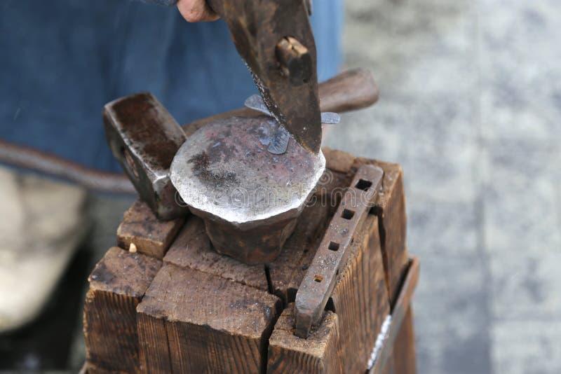 De houten lijst van bars van een boom wordt vastgemaakt door een grote steun en een aambeeld aan een hamer voor smeedt zaken stock foto's
