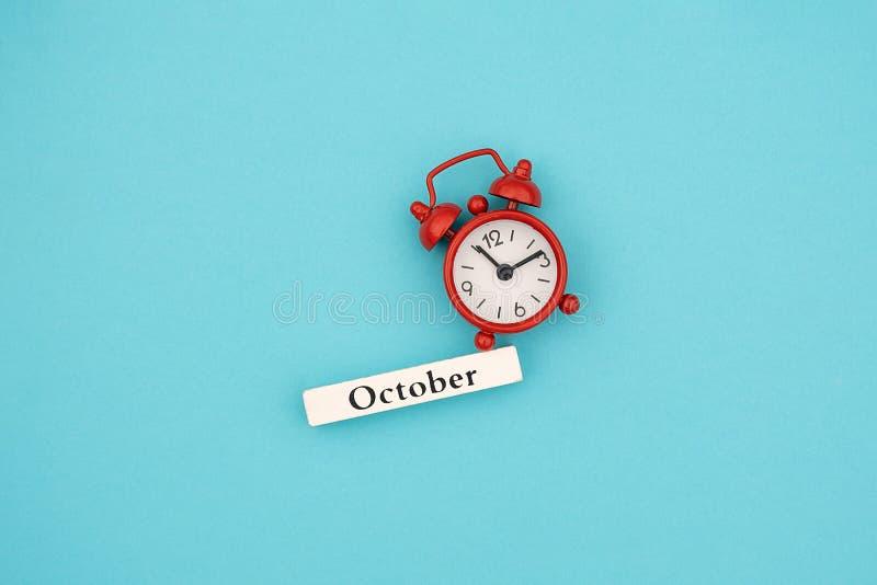 De houten maand Oktober van de kalenderherfst en rode wekker op blauwe document achtergrond Concept Hello September Creatieve Hoo stock fotografie