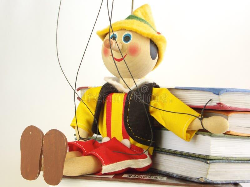 De houten marionet en de boeken stock foto