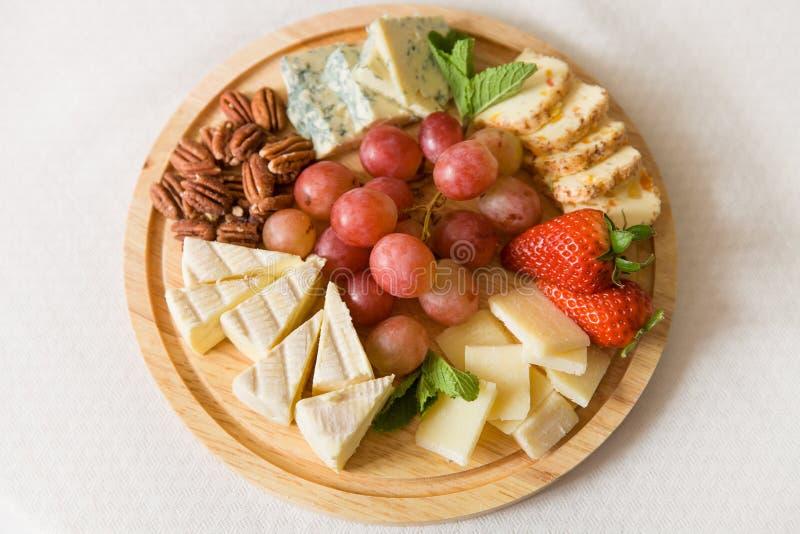 De houten plaat met heerlijke reeks kazen diende met organische druiven, pecannoten, aardbeien en munt royalty-vrije stock foto