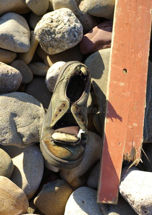 De de houten plank en schoen van het strandvuilnis op rotsachtige kust royalty-vrije stock fotografie