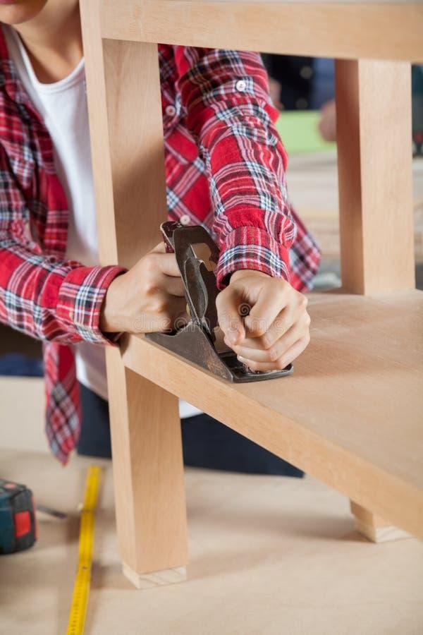 De Houten Plank van timmermansusing planer on stock afbeeldingen