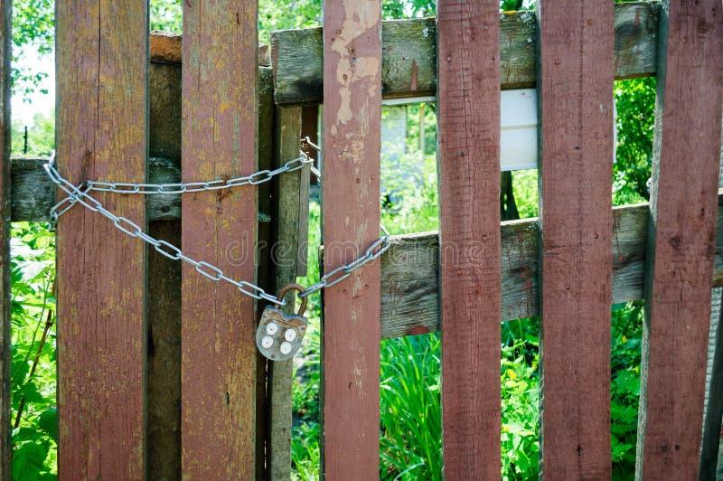 De houten poort is gesloten met een kettingsslot stock foto