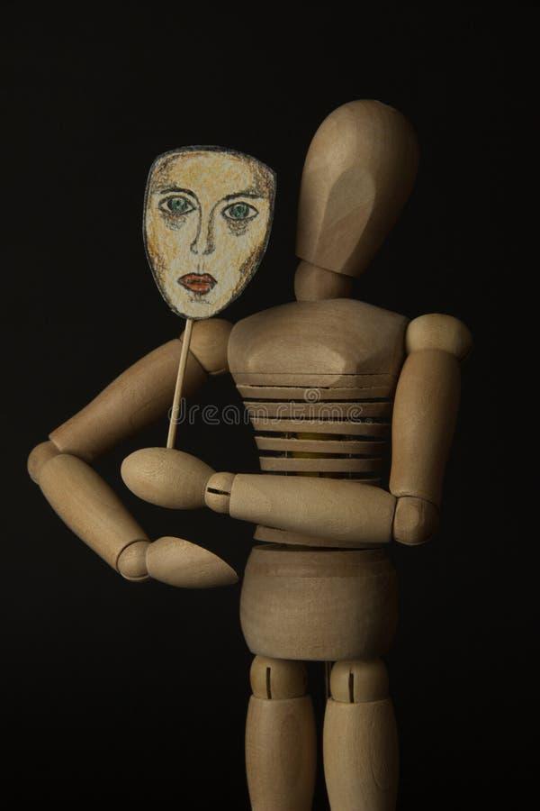 De houten pop op scharnieren houdt een masker in handen en behandelt haar gezicht royalty-vrije stock foto's