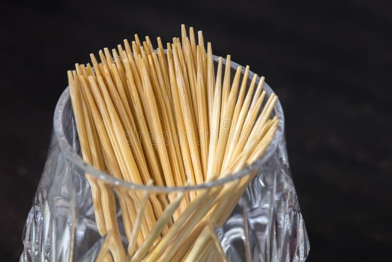 De houten tandenstokers in een glaskop zijn op de lijst, aangaande een donkere achtergrond mondelinge hygiëne na het eten royalty-vrije stock afbeeldingen