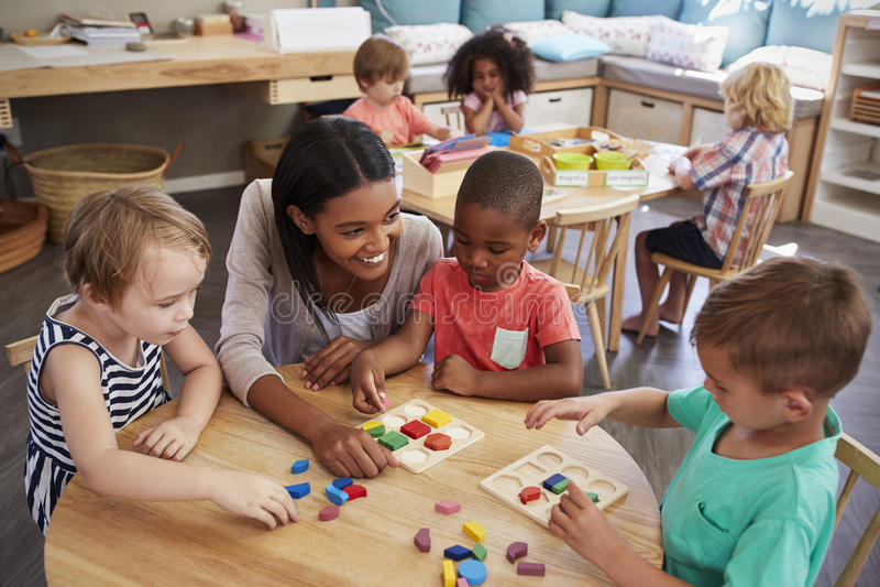 De Houten Vormen van leraarsand pupils using in Montessori-School royalty-vrije stock afbeelding