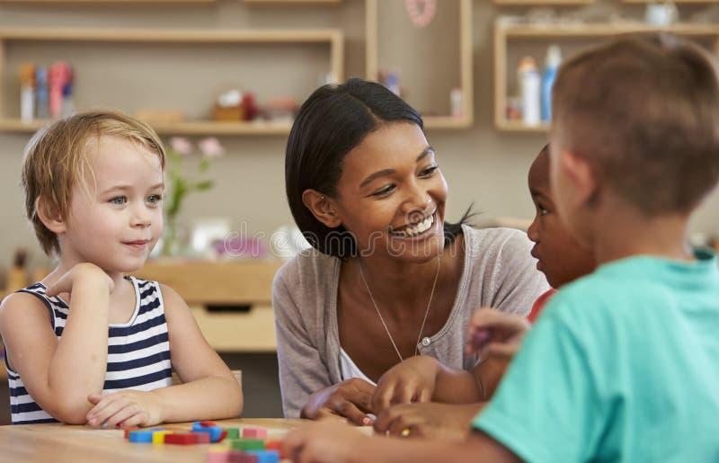 De Houten Vormen van leraarsand pupils using in Montessori-School stock afbeelding