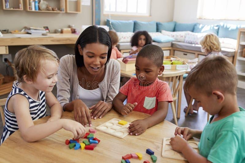 De Houten Vormen van leraarsand pupils using in Montessori-School royalty-vrije stock afbeeldingen
