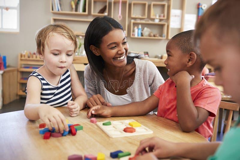 De Houten Vormen van leraarsand pupils using in Montessori-School stock afbeeldingen