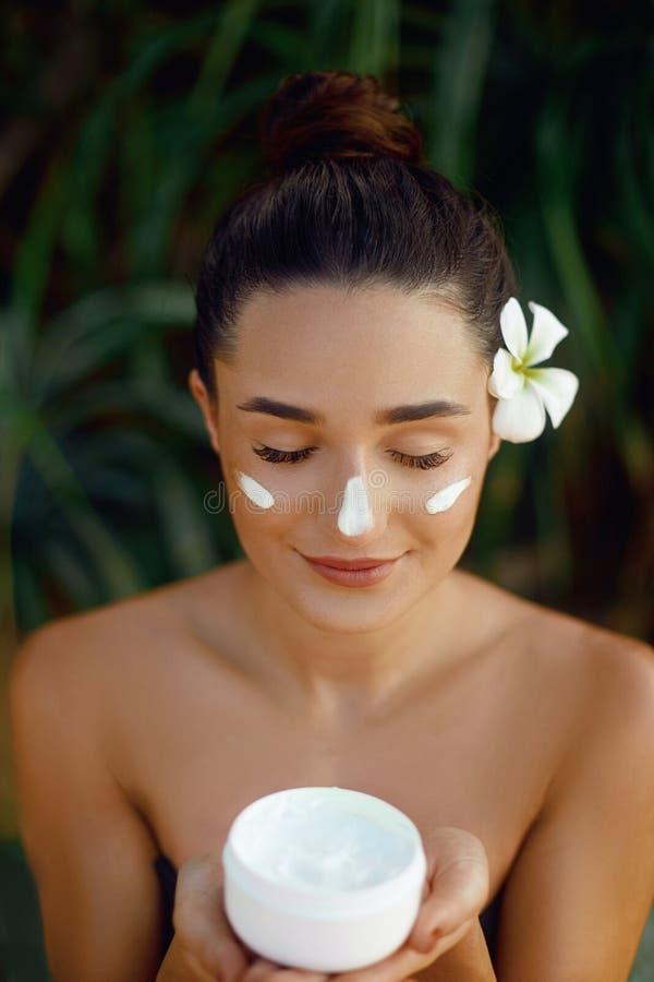 De huidzorg van het schoonheidsgezicht Mooie Vrouw met gezonde vlotte gezichts schone de flessen kosmetische room van de huidhold stock fotografie